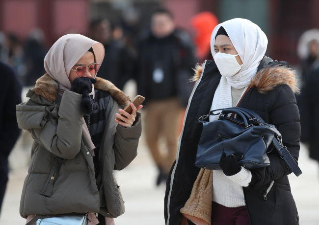 Tourists bundle up in central Seoul, Sunday. (Yonhap)