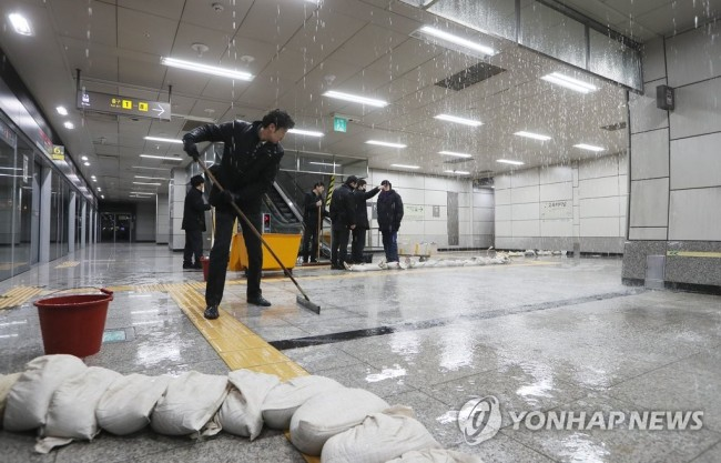 Workers mop up at Express Bus Terminal Station on Line No. 9, southern Seoul, Monday morning. (Yonhap)