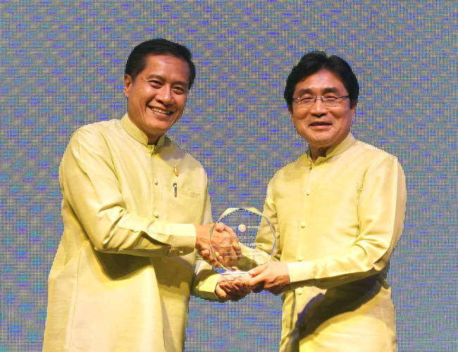 ASEAN-Korea Center Secretary-General Kim Young-sun (right) receives an award from Thai Minister of Tourism and Sports Weerasak Kowsurat for enhancing bilateral tourism at the 37th ASEAN Tourism Forum in Chiang Mai, Thailand, Friday. (ASEAN-Korea Center)