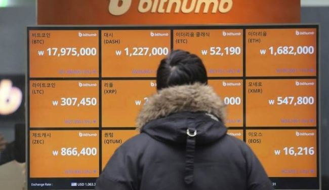 A client looks at the electronic signboard of a cryptocurrency exchange in Seoul. (AP)