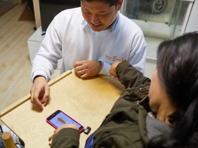 A SK Telecom employee helps a physically impaired person to operate the Smart Home system on a smartphone (SK Telecom)