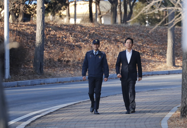 Samsung heir Lee Jae-yong (right) leaves the Seoul Detention House in Uiwang, Gyeonggi Province, on Monday as he was set free in an appeals trial. (Yonhap)