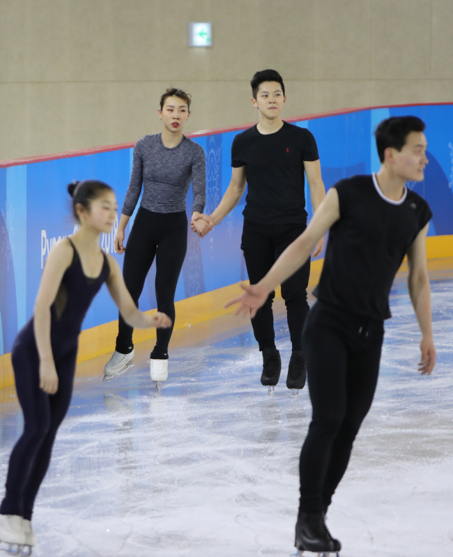 In the foreground are the North Korean Ryom Tae-ok (left) and Kim Ju-sik pair. In the background are the South Korean Kim Kyu-eun (left) and Kam Kang-chan pair.