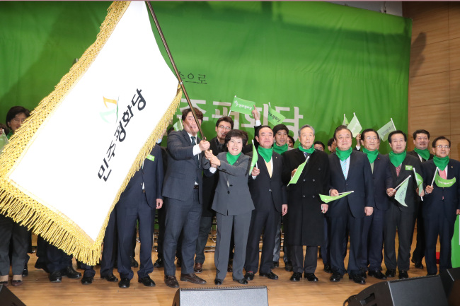 Cho Bae-sook, the leader of the new Party for Democracy and Peace, waves the party`s flag during a convention marking its creation at the National Assembly in Seoul on Tuesday. (Yonhap)