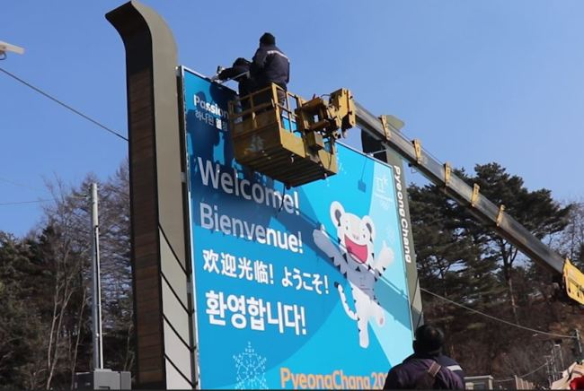 Construction workers work on a promotional board featuring PyeongChang Olympics mascots Soohorang and Bandabi installed on a roadside near the PyeongChang Olympic Plaza on Thursday. (Park Ju-young/The Korea Herald)