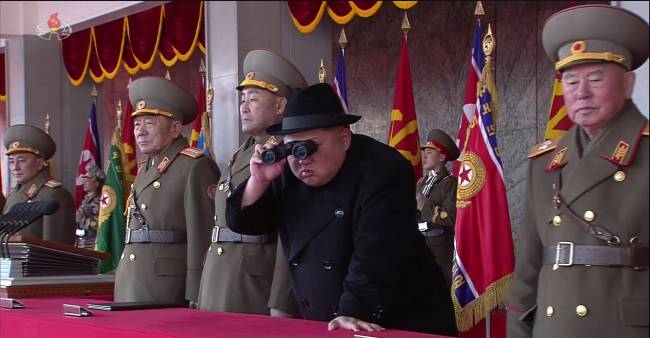 North Korean leader Kim Jong-un uses binoculars to look out at the military parade Thursday. (Yonhap)