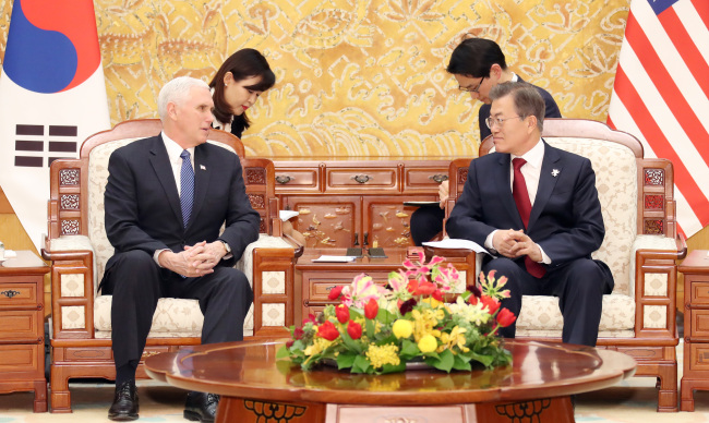 President Moon Jae-in and US Vice President Mike Pence talk at Cheong Wa Dae on Thursday. (Yonhap)