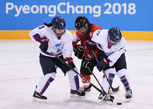 A player from Switzerland is being challenged by Korean hockey players Kim Se-rin and Randi Heesoo Griffin. (Yonhap)