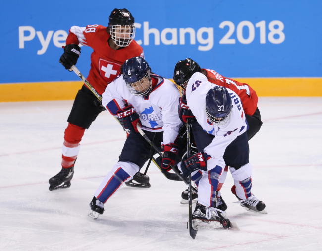Korean players Kim Se-lin (2nd from L) and Randi Heesoo Griffin (R) keep a Swiss player in check during the teams` Group B game of the women`s ice hockey tournament at the PyeongChang Winter Olympics in Gangneung, Gangwon Province, on Feb. 10, 2018. (Yonhap)