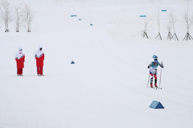 Two N. Korean coaches cheering South Korean skier Kim Eun-ho. (Yonhap)