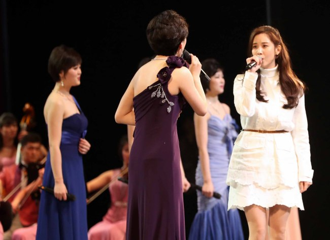"South Korea's K-pop star Seohyun (dressed in white) sings ""Our wish,"" a song that features the two Korea's yearning for unification, along with North Korean performers at the National Theater of Korea in Seoul on Sunday. (Yonhap)"