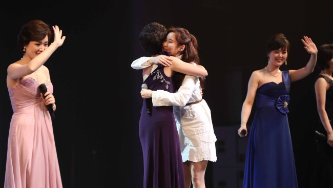 South Korea's K-pop star Seohyun (dressed in white) hugs a North Korean singer following a joint performance at the National Theater of Korea in Seoul on Sunday. (Yonhap)