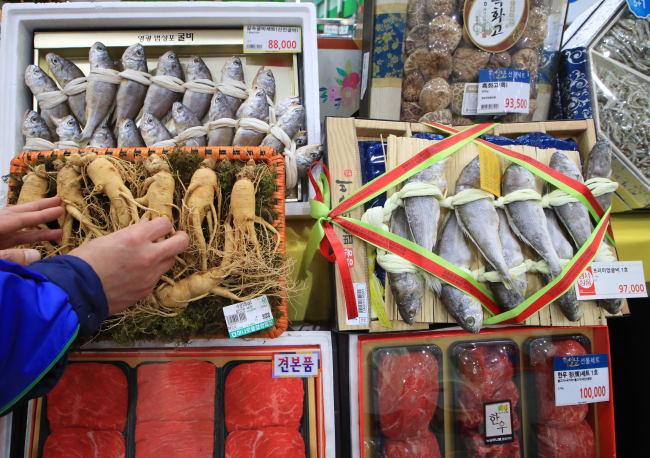 An employee at Hanaro Mart in Yangjae-dong, Seoul, adjusts a displayed gift set that comprises homegrown agricultural products to fit the revised limit of presents from 50,000 won to 100,000 won for the public sector. (Yonhap)