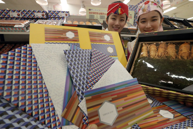 Models show envelopes designed for Saebaetdon, cash gifts exchanged among family members, as part of the Lunar New Year gift set sold at Emart in Seoul. (Yonhap)