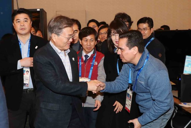 President Moon Jae-in is greeted by a foreign reporter during his visit to Gangneung Media Center on Saturday. (Yonhap)