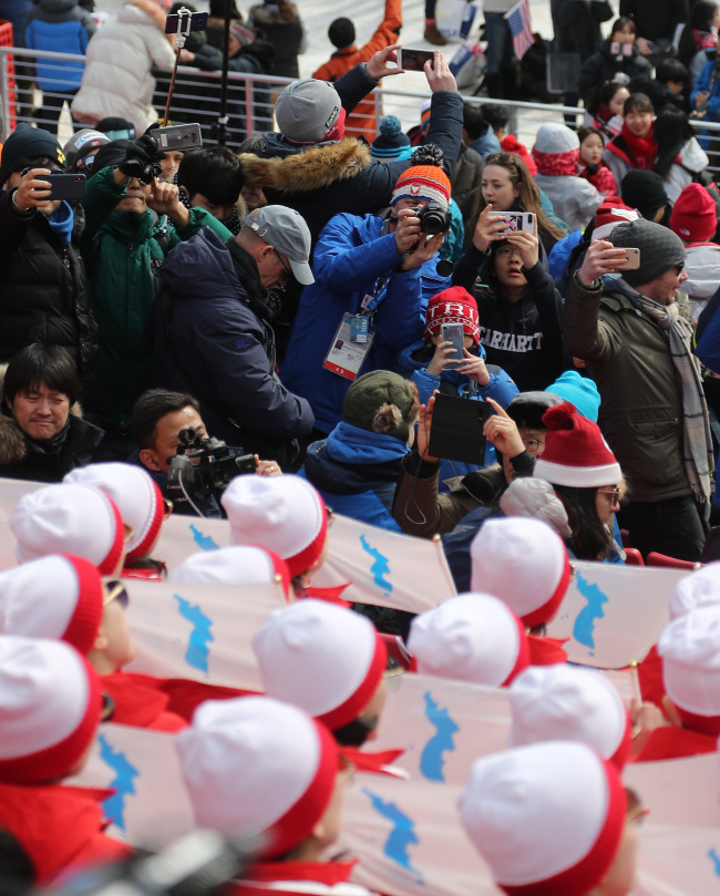 Spectators and reporters at the men's giant slalom games rush to take photos of the North Korean cheerleaders. Here, the cheerleaders are holding the Korean Unification Flag, which shows the image of a blue Korean Peninsula.