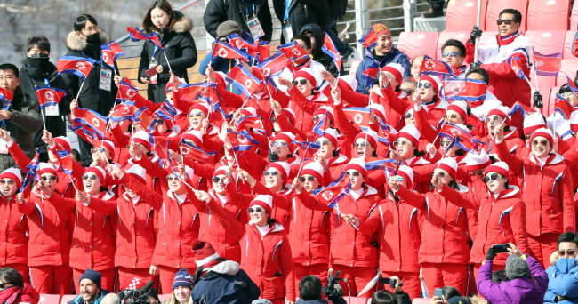 The cheerleading team hold the flag of North Korea while cheering at the men's giant slalom games.