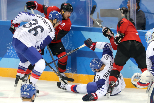 South Korea`s Park Woo-sang (L) and Lee Don-ku (2nd from R) go up against Canada during the teams` Group A match at Gangneung Hockey Centre in Gangneung, Gangwon Province, during the Winter Olympics on Sunday. (Yonhap)