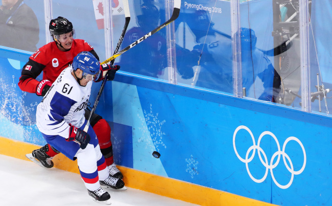 Korean defenseman Lee Don-ku (R) battles Canadian forward Mason Raymond for the puck in the teams` Group A match at Gangneung Hockey Centre in Gangneung, Gangwon Province, during the PyeongChang Winter Olympics on Feb. 18, 2018. (Yonhap)