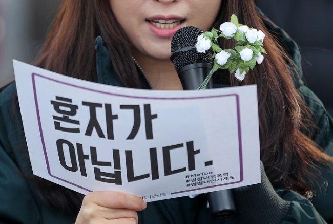 """A woman holds a sign reading """"You are not alone,"""" at a rally on Feb. 1 in Daegu to demand investigation into sexual violence in Korea's prosecution service. (Yonhap)"""