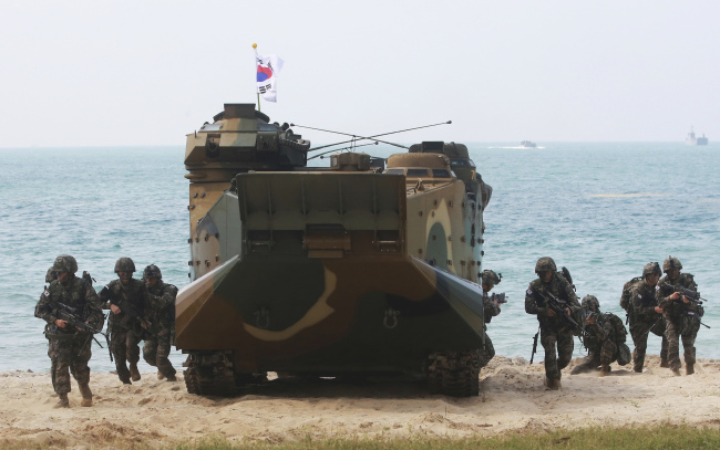 South Korean soldiers jump off an amphibious assault vehicle after hitting the ground during the ongoing Cobra Gold US-Thai joint military exercise on Hat Yao beach in Chonburi province, eastern Thailand, Saturday. AP-Yonhap