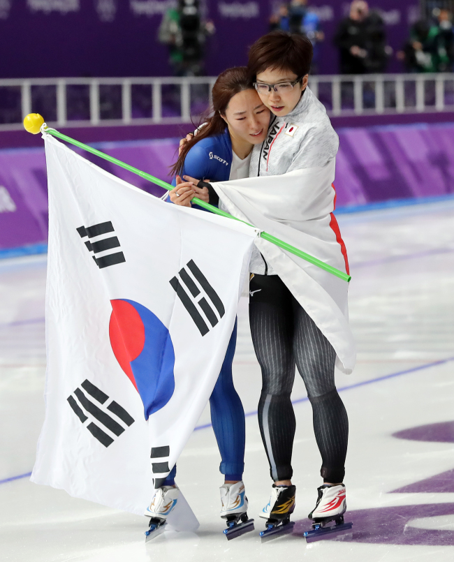 South Korea`s Lee Sang-hwa (left) is being comforted by Japan`s Nao Kodaira during their lap of honor at PyeongChang Winter Games on Sunday. Lee claimed her silver, while Kodaira won the gold in Women`s 500-meter speedskating final. (Yonhap)