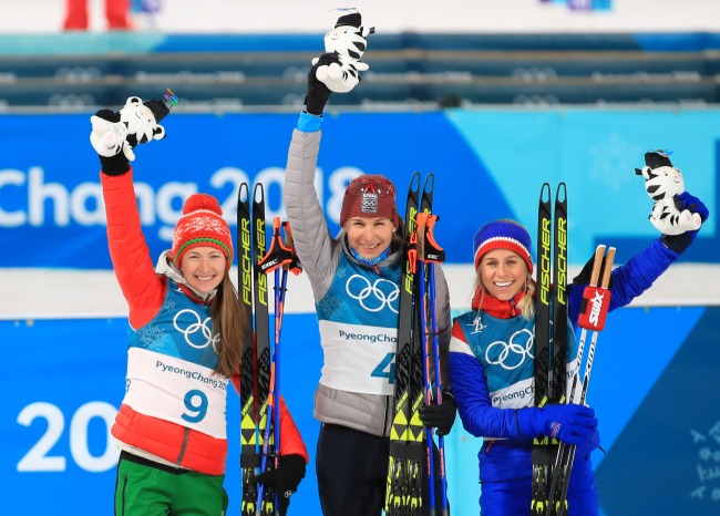 Winners of the women's 12.5-kilometer mass start event at the Winter Olympics hold up stuffed Soohorang dolls at the Alpensia Biathlon Centre in PyeongChang, Gangwon Province, on Saturday. From left are silver medalist Darya Domracheva from Belarus, gold medalist Anastasiya Kuzmina from Slovakia and bronze medalist Tiril Eckhoff of Norway. (Yonhap)