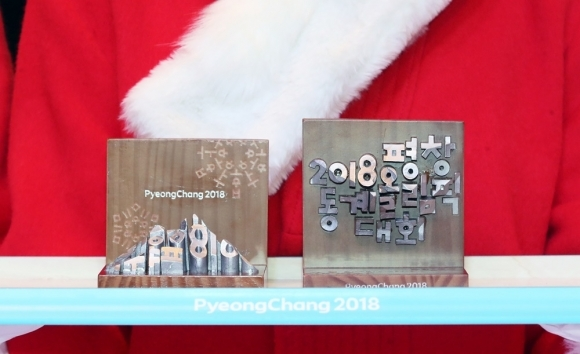 Square plaques are bestowed to Olympic medalists at the PyeongChang Winter Games. They combine wood and metal to form an image of the mountains of PyeongChang in 3-D. They also create snowflakes using letters from Hangeul, the Korean alphabet. (Yonhap)