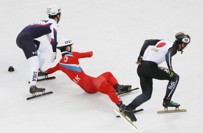 North Korean short track speed skater Jong Kwang-bom (C) falls down during a preliminary race in the men`s 500 meters at Gangneung Ice Arena in Gangneung during the PyeongChang Winter Olympics on Feb. 20, 2018. (Yonhap)
