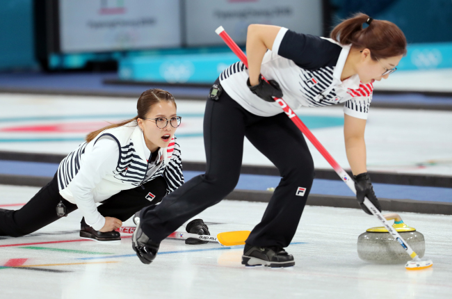 Kim Eun-jung (left), the skip of South Korea's women's curling team competes against OAR during a round-robin match held Wednesday. The game ended with Korea defeating OAR 11-2. (Yonhap)