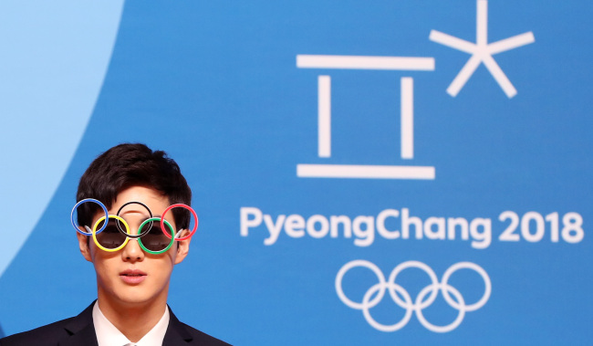 Suho, leader of K-pop group EXO, appears in front of reporters wearing sunglasses made of the five-ringed Olympic symbol at PyeongChang Olympic Main Press Centre at Alpensia Resort in PyeongChang on Feb. 21, 2018. (Yonhap)