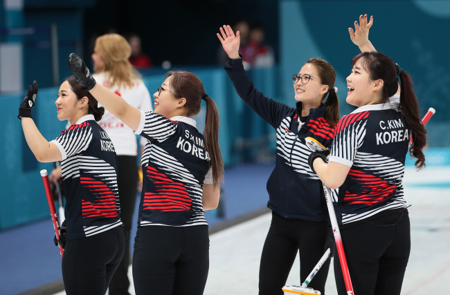 Members of the South Korean women`s curling team wave to spectators after defeating Denmark in a round-robin match held on Wednesday. (Yonhap)