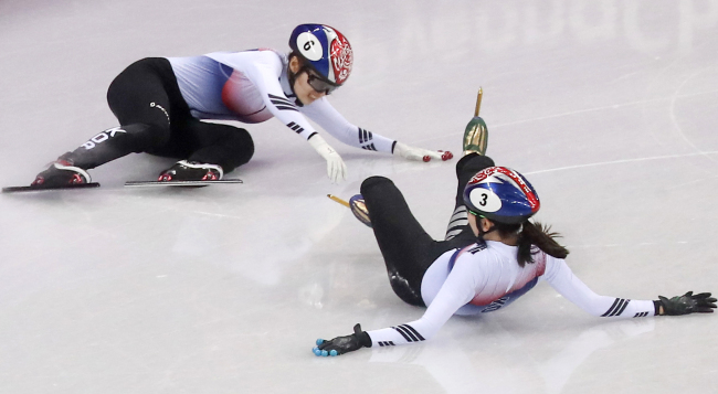 Korean short track speedskaters, Shim Suk-hee (right) and Choi Min-jeong, bumped each other and fell together in the race of the women's 1,000 meters at the Pyeongchang Olympics. (Yonhap)