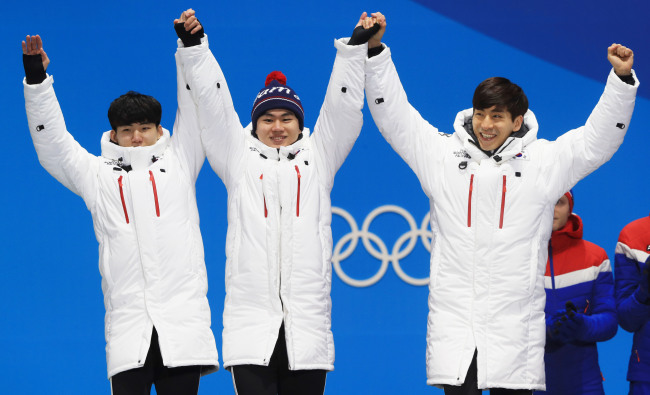 The trio of Lee Seung-hoon, Kim Min-seok and Chung Jae-won greet at the awards ceremony after winning silver in men's team pursuit speed skating in the PyeongChang Winter Games. (Yonhap)