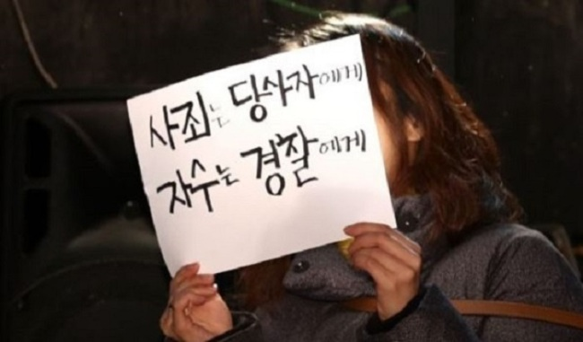 """A woman holds a banner reading, """"Apologize to the party concerned, surrender to the police"""" at a press conference to protest against theatrical director Lee Youn-taek in Seoul on Feb. 19. (Yonhap)"""