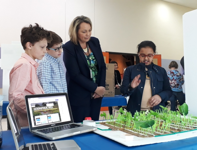 "Aashna Anand (far right), a fifth-grader at Korea International School, explains the prototype of her invention titled ""Recycled Farming"" to her peers and Pangyo Elementary principal Danielle Rich (second from right), at the Eco Trade Show held at the school compound in Seongnam, Gyeonggi Province, on Friday. (Korea International School)"
