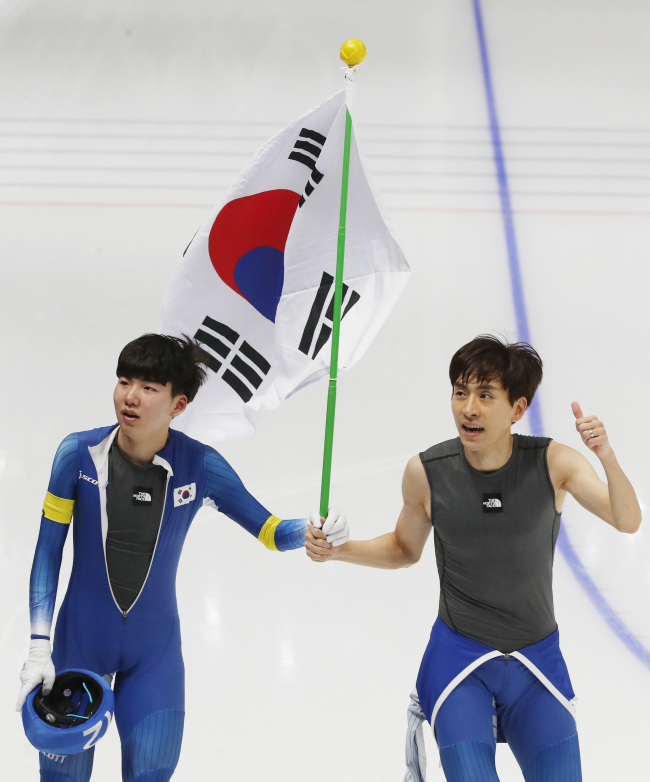 Chung Jae-won (left) holds the Korean flag with his teammate and gold-medalist Lee Seung-hoon (right) (Yonhap)
