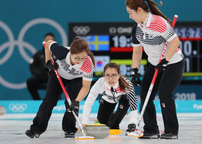Kim Seon-yeong (left), Kim Eun-jung (center) and Kim Yeong-mi (right) of South Korea's women's curling team compete in the final Olympic match against the Swedish team at the Gangneung Curling Centre in Gangneung, Gangwon Province, Sunday. Sweden won the match 8-3 to take gold, with Korea taking silver. (Yonhap)