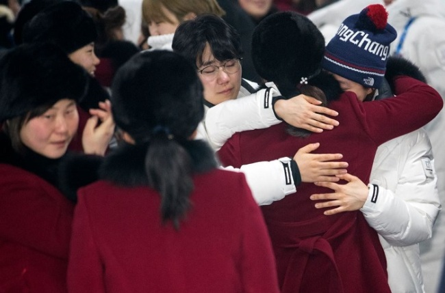 Players of the unified Korean women`s hockey team exchange hugs at Gangneung Olympic Village in Gangneung, Gangwon Province, before the North Korean players (in burgundy coats) left South Korea on Feb. 26, 2018, a day after the closing ceremony of the PyeongChang Winter Olympics. (Yonhap)