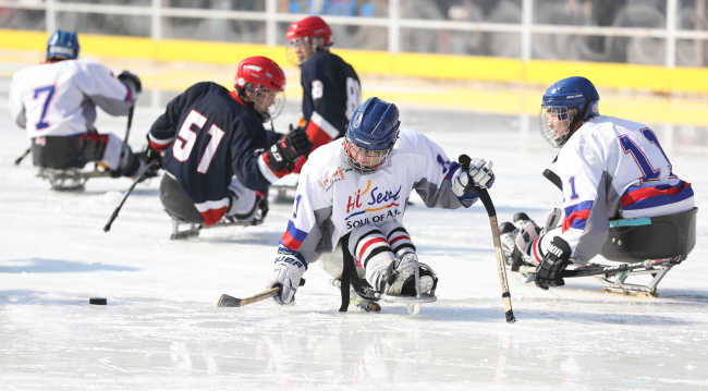 Para ice hockey players compete in an exhibition match at a special ice rink in front of Seoul City Hall in Seoul to promote the PyeongChang Paralympic Winter Games on Monday. (Yonhap)