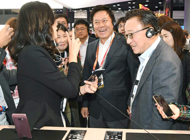 SK Telecom CEO Park Jung-ho (center) and DJ Koh (right), president and Head of IT & Mobile Communications Division, Samsung Electronics, look at Samsung`s Galaxy S9 at the tech firm`s booth at Mobile World Congress in Barcelona, Spain, Monday. (SK Telecom)