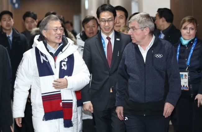 South Korean President Moon Jae-in, left, and IOC President Thomas Bach walk together to enter the Olympics` closing ceremony on Sunday. (Yonhap)