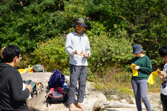 Kim Young-seog, geology professor at Pukyong National University, gives a field lecture in a valley in South Gyeongsang Province. (Courtesy of Kim Young-seog)
