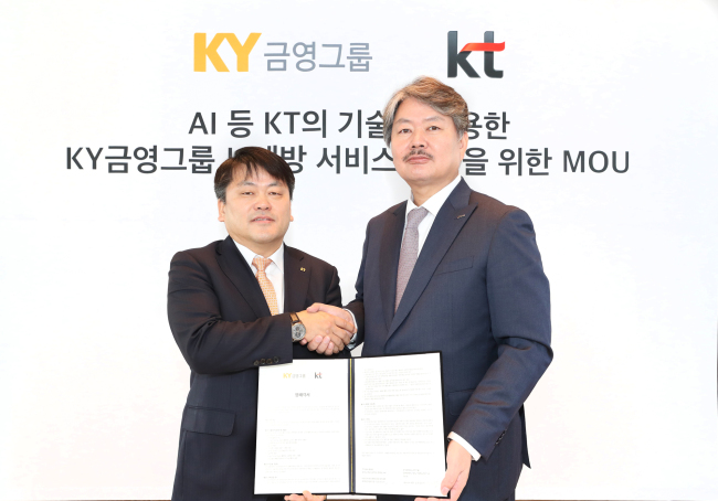 Kim Won-kyung, head of marketing strategy for KT (left) and Kim Jin-gap, president of Kumyoung Group, shake hands at a signing ceremony at KT's offices in Jongno-gu, Seoul. (hjwon@heraldcorp.com)