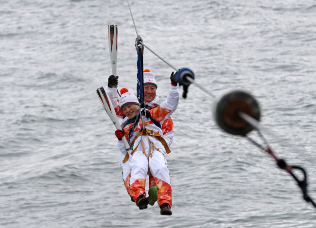 The torch for the PyeongChang Paralympics arrives in Gangneung via the Aranabi zip-line on Thursday.