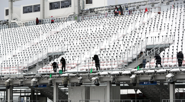 Staff clean snow from PyeongChang Olympic Stadium ahead of the Paralympic opening ceremony.