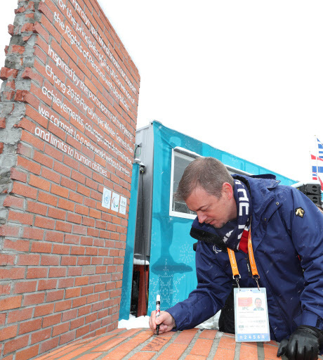 International Paralympic Committee President Andrew Parsons signs on the Paralympic Mural on Thursday.