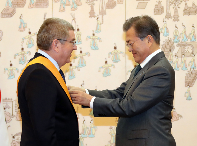 President Moon Jae-in (right) confers the Cheongryong Medal on IOC chief Thomas Bach at Cheong Wa Dae on Thursday. (Yonhap)