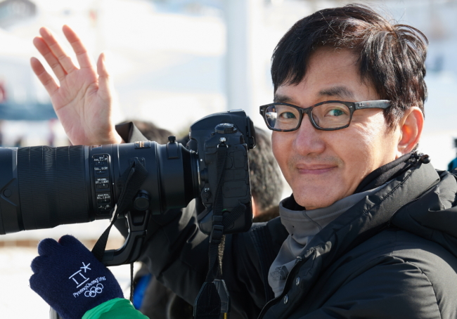 Photographer Cho Sei-hon waves while taking a photo at an outdoors venue. (Icon Studio)