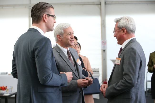 SK Innovation CEO Kim Jun (right) talks with officials from global car companies during a groundbreaking ceremony for the firm's plant in Hungary on Thursday. (SK Innovation)